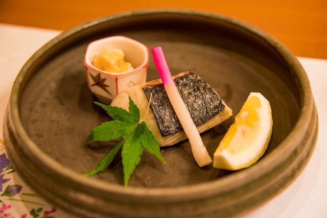 切り身の焼き魚の上のはじかみと飾り葉。