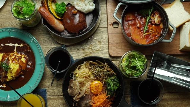 木製カッティングボードや鋳物の鍋に盛り付けられた温かみのある料理
